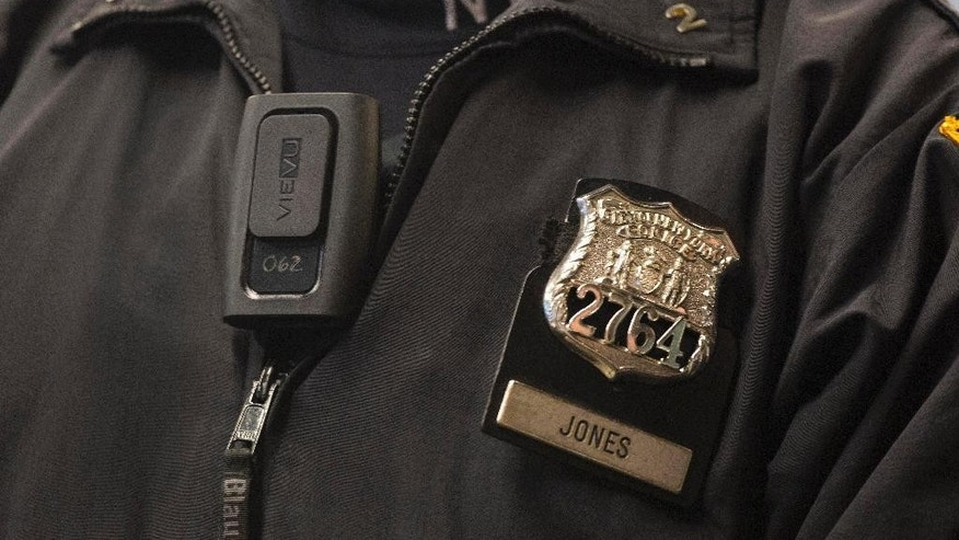 FILE - In this Dec. 3, 2014, file photo, New York Police Department Officer Joshua Jones wears a VieVu body camera on his chest during a news conference in New York. Police departments across the country are altering policies and procedures to assuage concerns about police conduct and to protect their own officers. In New York, they'll make greater use of stun guns; and body cameras are becoming more common in all departments. (AP Photo/Mark Lennihan, File)