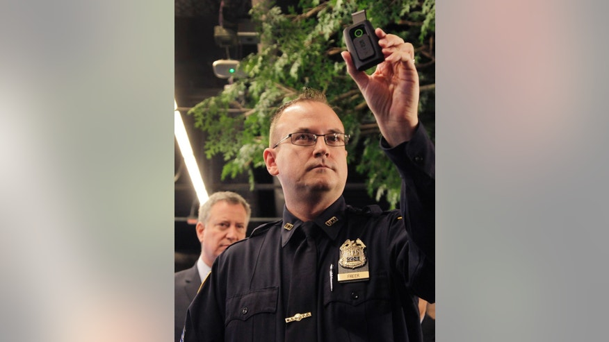 FILE - In this Dec. 3, 2014, file photo, New York Police Department Sgt. Joseph Freer holds a body camera during a news conference while Mayor Bill de Blasio listens, in New York. Police departments across the country are altering policies and procedures to assuage concerns about police conduct and to protect their own officers. In New York, they'll make greater use of stun guns; and body cameras are becoming more common in all departments. (AP Photo/Mark Lennihan, File)