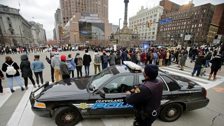 FILE - In this Nov. 25, 2014, file photo, Cleveland police watch demonstrators block Public Square in the city during a protest over the weekend police shooting of 12-year-old Tamir Rice. In cities and states nationwide, police departments are already altering policies and procedures to temper concerns about police conduct in the aftermath of recent cases of black males dying at the hands of white officers. (AP Photo/Mark Duncan, File)