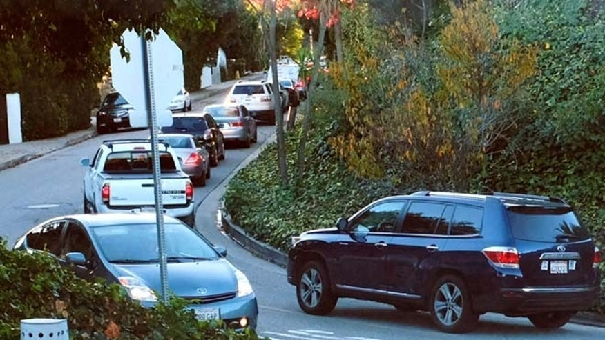 Dec. 9, 2014: Early morning rush hour traffic winds it's way along a narrow street in Sherman Oaks section of Los Angeles. When the people whose houses hug the narrow warren of streets paralleling the busiest urban freeway in America began to see bumper-to-bumper traffic rushing by their homes a year or so ago they were baffled. When word spread that the explosively popular new smartphone app Waze was sending many of those cars through their neighborhood in a quest to shave five minutes off a daily rush-hour commute, they were angry and ready to fight back.