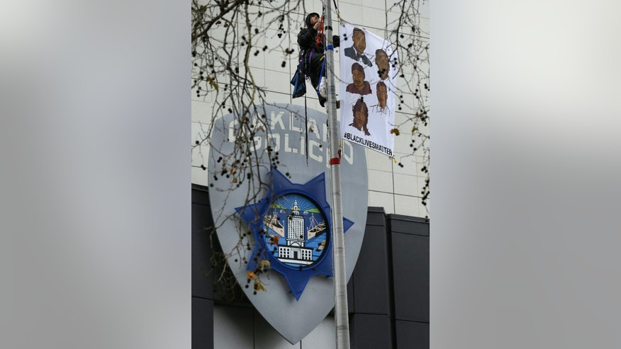 "A protestor hangs a banner which reads ""Black Lives Matter,"" atop the flagpole of the Oakland Police Department, Monday, Dec. 15, 2014, in Oakland, Calif. Demonstrators blocked streets around Oakland police headquarters and chained themselves to the front of the building Monday to protest recent grand jury decisions not to indict white officers who killed unarmed black men in Ferguson, Mo., and New York. (AP Photo/Ben Margot)"