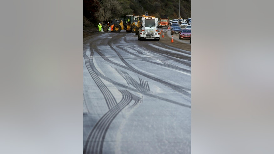 Caltrans crews work to clean up a torrent of mud and rocks covering part of State Route 91 in Orange County early Wednesday, Dec. 17, 2014, in Yorba Linda, Calif. Cars and trucks were stuck for several hours, but no injuries were reported. (AP Photo/Chris Carlson)