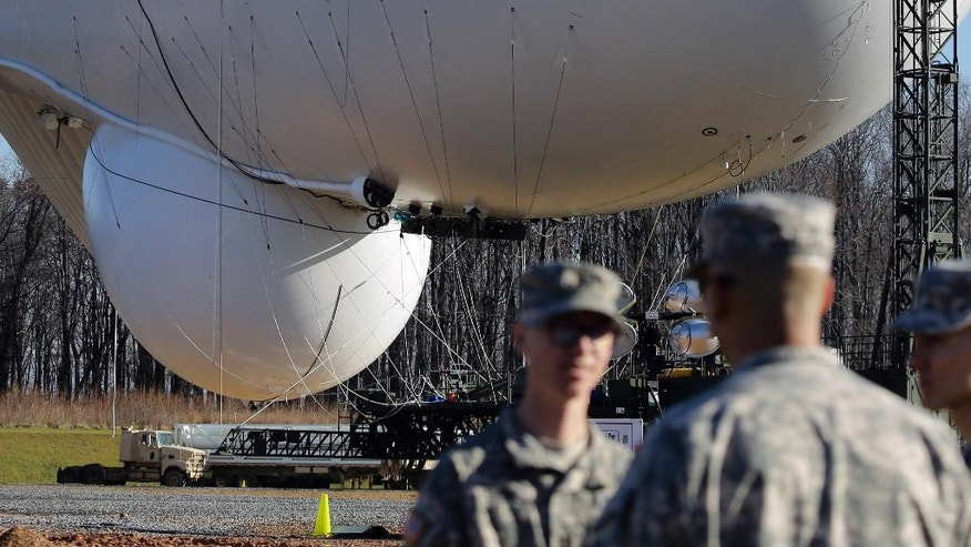 A giant radar dome is seen on the bottom of an unmanned aerostat that is part of a new U.S. military cruise-missile defense system during a media preview, Wednesday, Dec. 17, 2014, in Middle River, Md. Military officials said a pair of helium-filled aerostats stationed in Maryland are intended provide early detection of cruise missiles over a large swath of the East Coast, from Norfolk, Va., to upstate New York, during a three-year test. JLENS, short for Joint Land Attack Cruise Missile Defense Elevated Netted Sensor System, will be fully implemented this winter. (AP Photo/Patrick Semansky)