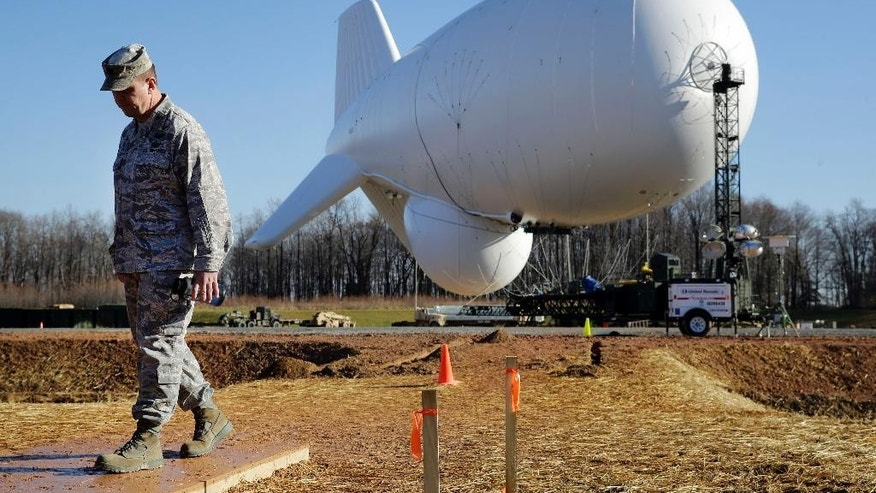 U.S. Air Force Col. William Pitts walks in front of an unmanned aerostat that is part of a new U.S. military cruise-missile defense system during a media preview, Wednesday, Dec. 17, 2014, in Middle River, Md. Military officials said a pair of helium-filled aerostats stationed in Maryland are intended provide early detection of cruise missiles over a large swath of the East Coast, from Norfolk, Va., to upstate New York, during a three-year test. JLENS, short for Joint Land Attack Cruise Missile Defense Elevated Netted Sensor System, will be fully implemented this winter. (AP Photo/Patrick Semansky)