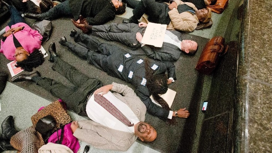 """A group including lawyers Michael Coard, center face down, Lloyd Long III, center with sign, and others stage a 4:30 minute """"die-in"""" protest Wednesday, Dec. 17, 2014, at the criminal justice center in Philadelphia. A number of protests have been staged around the country following recent grand jury decisions not to indict white police officers in New York and Ferguson, Mo., over the deaths of unarmed black men.  (AP Photo/Matt Rourke)"""