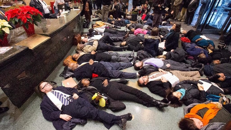 """A group including attorney Leo M. Mulvihill, Jr., foreground, lawyers and others stage a 4:30 minute """"die-in"""" protest Wednesday, Dec. 17, 2014, at the criminal justice center in Philadelphia. A number of protests have been staged around the country following recent grand jury decisions not to indict white police officers in New York and Ferguson, Missouri, over the deaths of unarmed black men.  (AP Photo/Matt Rourke)"""
