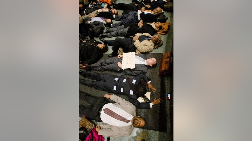 """A group including lawyers Michael Coard, center face down, Lloyd Long III, center with sign, others stage a 4:30 minute """"die-in"""" protest Wednesday, Dec. 17, 2014, at the criminal justice center in Philadelphia. A number of protests have been staged around the country following recent grand jury decisions not to indict white police officers in New York and Ferguson, Missouri, over the deaths of unarmed black men.  (AP Photo/Matt Rourke)"""