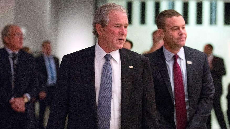 In this photo taken on Sunday, Dec. 14, 2014 and provided by the National September 11 Memorial and Museum, former President George W. Bush, center, makes an unannounced visit to the National September 11 Memorial & Museum in New York. At right is National September 11 Memorial & Museum President Joe Daniels. (AP Photo/National September 11 Memorial & Museum, Jin Lee)