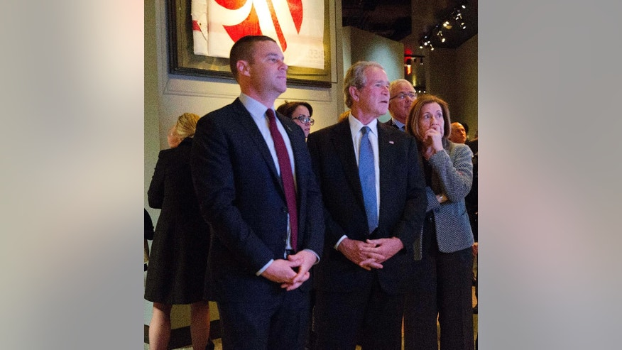 In this photo taken on Sunday, Dec. 14, 2014 and provided by the National September 11 Memorial and Museum, former President George W. Bush, center, makes an unannounced visit to the National September 11 Memorial & Museum in New York. At left is National September 11 Memorial & Museum President Joe Daniels, and at right is museum Director Alice Greenwald. (AP Photo/National September 11 Memorial & Museum, Jin Lee)