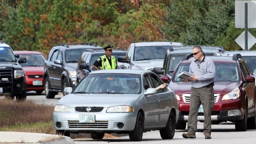 FILE - In this photo taken Oct. 16, 2013 in North Conway, N.H., local and state police with FBI agents set up a road block questioning drivers on the road in North Conway, N.H., where a 14-year-old would have walked home from school.  Nathaniel Kibby has been indicted on charges he kidnapped the 14-year-old girl, imprisoned her and sexually assaulted her over nine months. Two courts on Wednesday Dec. 17, 2014 released indictments on 200-plus counts charging Kibby with kidnapping, sexual assault and criminal threatening, among others. He has been jailed on $1 million bail since his arrest. (AP Photo/FILE)