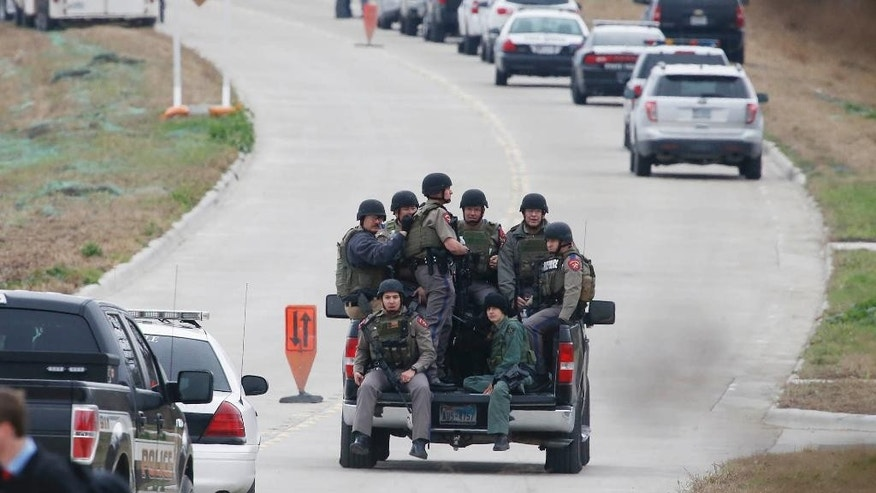 Texas Department of Public Safety officers ride in a pickup to a command post while other officers look for a gunman who shot a weather forecaster during an altercation outside the KCEN-TV studio along Interstate 35 between Waco and Temple, Wednesday, Dec. 17, 2014 in Bruceville-Eddy, Texas. (AP Photo/Waco Tribune Herald, Rod Aydelotte)
