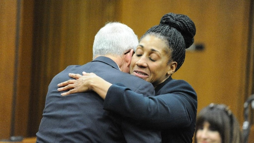 Wayne County Assistant Prosecutor Lisa Lindsey hugs defense attorney Mike McCarthy after five guilty verdicts were delivered against Bob Bashara at the Frank Murphy Hall of Justice in Detroit on Thursday, Dec. 18, 2014. Bashara was found guilty on all five counts for hiring handyman Joseph Gentz to kill his wife Jane Bashara. The trial revealed his secret life: a former Rotary Club president who used cocaine and hosted men and women at a sex dungeon under a bar. (AP Photo/The Detroit News, David Coates)
