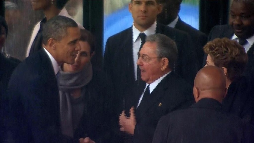 "FILE - In this Dec. 10, 2013 file image from TV, U.S. President Barack Obama shakes hands with Cuban President Raul Castro at the FNB Stadium in Soweto, South Africa, in the rain for a memorial service for former South African President Nelson Mandela. Obama on Wednesday, Dec. 17, 2014 declared the end of America's ""outdated approach"" to Cuba, announcing the re-establishment of diplomatic relations as well as economic and travel ties with the communist island — a historic shift in U.S. policy that aims to bring an end to a half-century of Cold War enmity. (AP Photo/SABC Pool, File)"