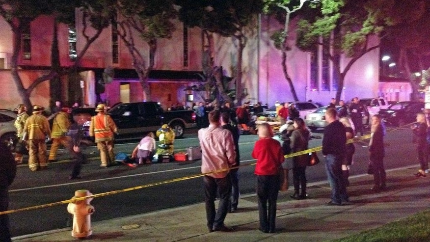 In this photo provided by Mark Milutin, firefighters work on a victim at left after a driver suspected of being intoxicated hit a group of pedestrians and another car outside a church as a Christmas service ended in the Los Angeles suburb of Redondo Beach, Calif., Wednesday evening, Dec. 17, 2014.  Three people were killed and several others were injured including five children, police said. Margo Bronstein, 56, was arrested after the crash on suspicion of driving under the influence and vehicular manslaughter, Redondo Beach police Lt. Shawn Freeman said. (AP Photo/Mark Milutin)