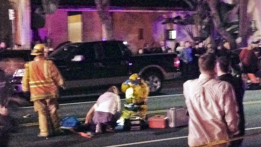 In this photo provided by Mark Milutin, firefighters work on a victim after a driver suspected of being intoxicated hit a group of pedestrians and another car outside a church as a Christmas service ended in the Los Angeles suburb of Redondo Beach, Calif., Wednesday evening, Dec. 17, 2014.  Three people were killed and several others were injured including five children, police said. Margo Bronstein, 56, was arrested after the crash on suspicion of driving under the influence and vehicular manslaughter, Redondo Beach police Lt. Shawn Freeman said. (AP Photo/Mark Milutin)