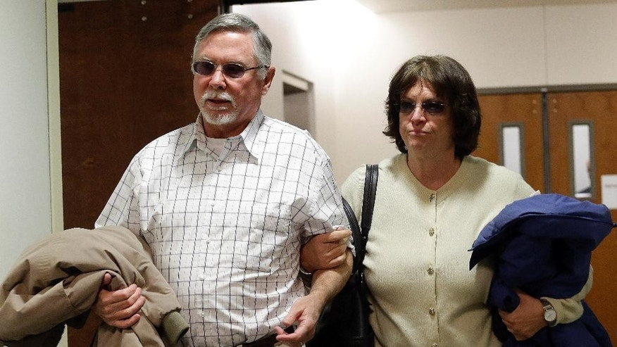 FILE - In this March 12, 2013, file photo, Robert and Arlene Holmes, the parents of Aurora theater shooting suspect James Holmes, arrive at district court for the arraignment of their son in Centennial, Colo. Robert and Arlene Holmes are asking that their son not receive the death penalty. Jury selection is scheduled to begin in January 2015, for the 2012 attack in Aurora that killed 12 people and injured 70. (AP Photo/Ed Andrieski, File)