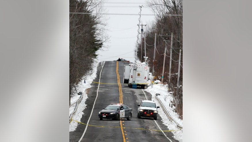 Police vehicles block the road on Friday, Dec. 19, 2014, near the home where a 5-year-old boy was abducted on Thursday, in Berne, N.Y.  Albany County Sheriff Craig Apple told local media at about 3 a.m. Friday that the body of Kenneth White was found by a sheriff's K-9 unit conducting a search in the rural hamlet of Clarksville, 10 miles southwest of Albany. No other details have been released. (AP Photo/Mike Groll)