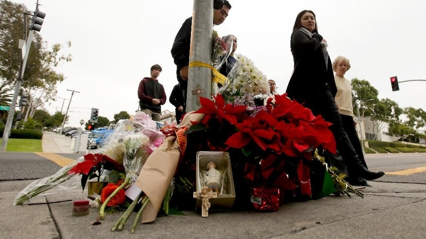 Church goers pass by a make shift memorial Thursday, Dec. 18, 2014 near where a driver suspected of being intoxicated hit a group of pedestrians and another car outside a church as a Christmas service ended Wednesday night in Redondo Beach, Calif. Three people were killed and several others were injured including five children, police said. Margo Bronstein, 56, was arrested after the crash on suspicion of driving under the influence and vehicular manslaughter, Redondo Beach police Lt. Shawn Freeman said. (AP Photo/Chris Carlson)