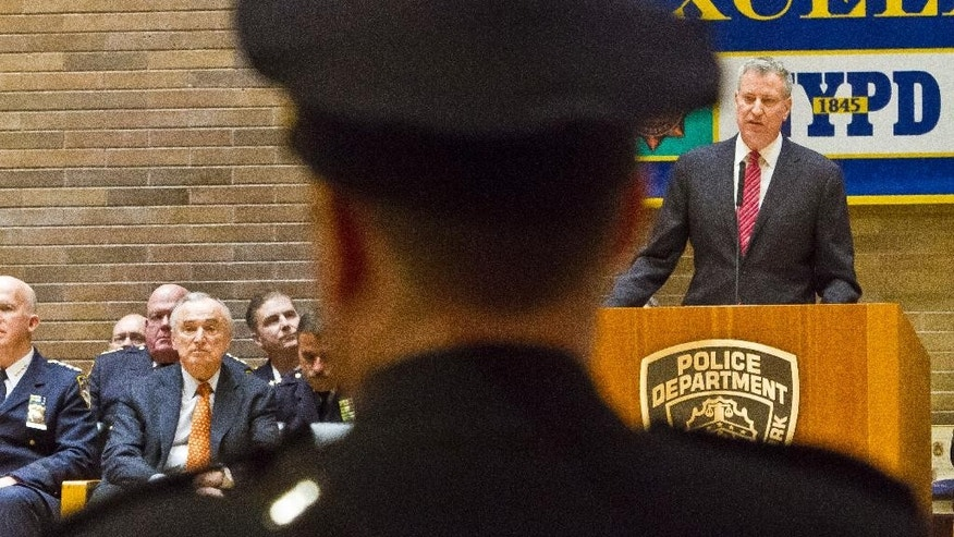 Commissioner Bill Bratton, fourth from left, sit among police officials listening as Mayor Bill de Blasio, far right, new NYPD detectives during a promotions ceremony, Friday, Dec. 19, 2014, in New York.  Even as New York's police department takes heat for its tactics in the outrage over the Eric Garner chokehold case, year-end crime statistics show two clear trends: low-level arrests are holding steady and overall crime continues to fall.  (AP Photo/Bebeto Matthews)