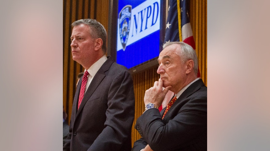 Mayor Bill de Blasio, left, and NYPD Commissioner Bill Bratton, right, listen during a press conference after attending a promotion ceremony for police officers, Friday, Dec. 19, 2014, in New York.  Even as New York's police department takes heat for its tactics in the outrage over the Eric Garner chokehold case, year-end crime statistics show two clear trends: low-level arrests are holding steady and overall crime continues to fall.  (AP Photo/Bebeto Matthews)