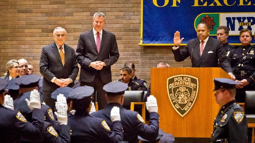 Commissioner Bill Bratton, standing left, Mayor Bill de Blasio, center, watch as Deputy Police Commissioner Benjamin Tucker, right, swears in new NYPD detective during a promotions ceremony, Friday, Dec. 19, 2014, in New York.  Even as New York's police department takes heat for its tactics in the outrage over the Eric Garner choke hold case, year-end crime statistics show two clear trends: low-level arrests are holding steady and overall crime continues to fall.  (AP Photo/Bebeto Matthews)