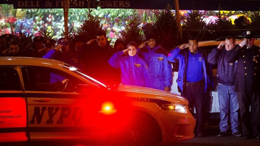 ADDS BOTH OFFICERS KILLED - Mourners stand at attention as the bodies of two fallen NYPD police officers are transported from Woodhull Medical Center, Saturday, Dec. 20, 2014, in New York. An armed man walked up to two New York Police Department officers sitting inside a patrol car and opened fire Saturday afternoon, killing both officers before running into a nearby subway station and committing suicide, police said. (AP Photo/John Minchillo)