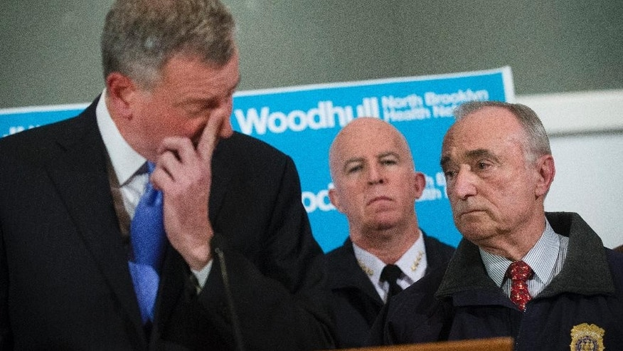 ADDS BOTH OFFICERS KILLED - NYPD Commissioner Bill Bratton, right, stands beside Mayor Bill de Blasio as he wipes his eye during a news conference at Woodhull Medical Center, Saturday, Dec. 20, 2014, in New York.  An armed man walked up to two New York Police Department officers sitting inside a patrol car and opened fire Saturday afternoon, killing both officers before running into a nearby subway station and committing suicide, police said. (AP Photo/John Minchillo)