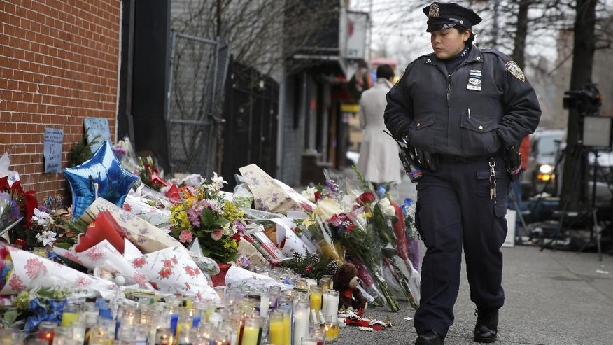 A New York City police officer looks over a makeshift memorial near the site where fellow officers Rafael Ramos and Wenjian Liu were murdered in the Brooklyn borough of New York, Monday, Dec. 22, 2014. Police say Ismaaiyl Brinsley ambushed the two officers in their patrol car in broad daylight Saturday, fatally shooting them before killing himself inside a subway station. (AP Photo/Seth Wenig)