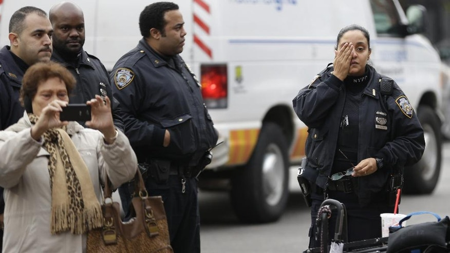 A New York City police officer wipes away tears while visiting a makeshift memorial near the site where fellow officers Rafael Ramos and Wenjian Liu were murdered in the Brooklyn borough of New York, Monday, Dec. 22, 2014. Police say Ismaaiyl Brinsley ambushed the two officers in their patrol car in broad daylight Saturday, fatally shooting them before killing himself inside a subway station. (AP Photo/Seth Wenig)