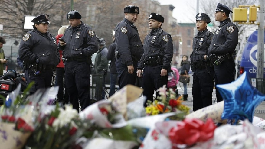 New York City police officers gather near a makeshift memorial near the site where fellow officers Rafael Ramos and Wenjian Liu were murdered in the Brooklyn borough of New York, Monday, Dec. 22, 2014. Police say Ismaaiyl Brinsley ambushed the two officers in their patrol car in broad daylight Saturday, fatally shooting them before killing himself inside a subway station. (AP Photo/Seth Wenig)