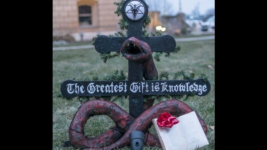 "Dec. 21, 2014: A ""Snaketivity"" scene featuring a snake offering a book called ""Revolt of the Angels"" as a gift is on display on the grounds of the Capitol in Lansing, Mich. Satanic Temple spokeswoman Jex Blackmore says in a videotaped interview with the Lansing State Journal that her group doesn't worship Satan but promotes individuality, compassion and views that differ from Christian and conservative beliefs."