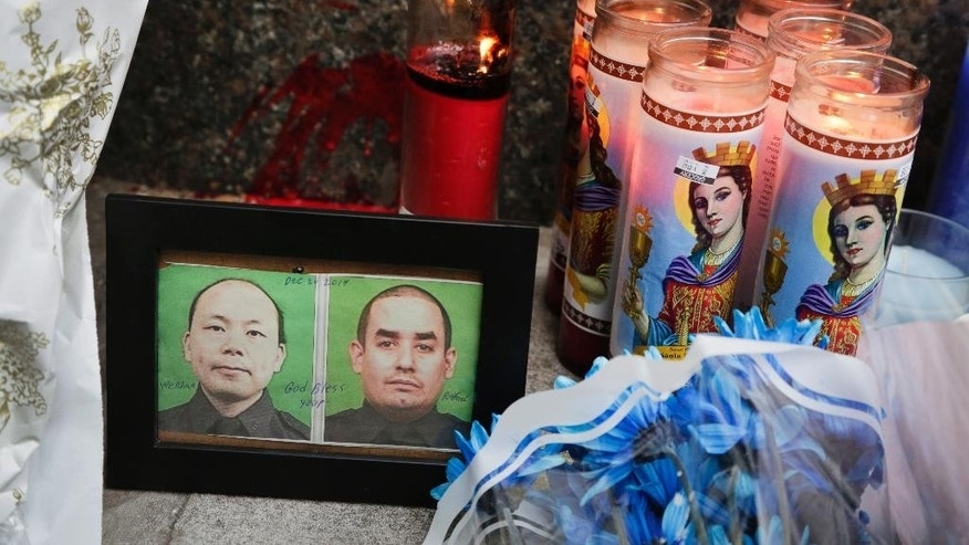 "Photographs of slain New York Police officers Wenjian Liu, left, and Rafael Ramos are placed in a makeshift memorial honoring the men at the 84th Precinct in the Brooklyn borough of New York, where the officers were stationed, Sunday, Dec. 21, 2014. Ismaaiyl Brinsley, who vowed online to shoot two ""pigs"" in retaliation for the police chokehold death of Eric Garner, ambushed  Ramos and Liu in a patrol car Saturday and fatally shot them in broad daylight before running to a subway station and killing himself, authorities said. (AP Photo/Mark Lennihan)"