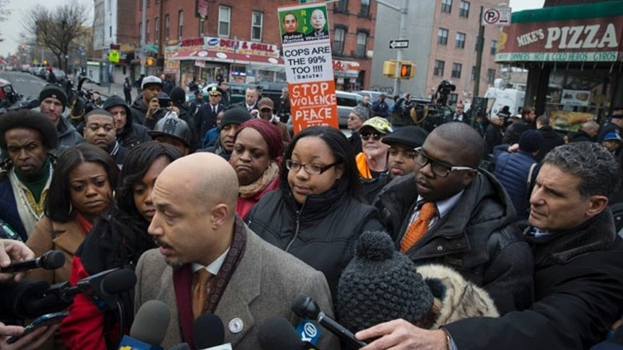 Dec. 22, 2014: Emerald Garner, daughter of Eric Garner, center, stands with National Action Network members near a makeshift memorial at the site where New York Police Department officers Rafael Ramos and Wenjian Liu were murdered in the Brooklyn borough of New York. (AP Photo/John Minchillo)