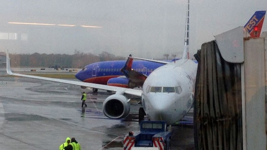 Dec. 23, 2014: In this photo taken through a window and provided by Jenny Kao, a Southwest Airlines plane, rear, and an American Airlines plane sit on the tarmac after a wingtip on the Southwest plane was ripped off when the aircrafts collided at La Guardia Airport in New York.