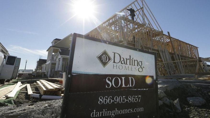 In this Dec. 15, 2014 photo, a sold sign sits in front of a house under construction in Coppell, Texas. The Commerce Department reports on sales of new homes in November on Tuesday, Dec. 23, 2014. (AP Photo/LM Otero)