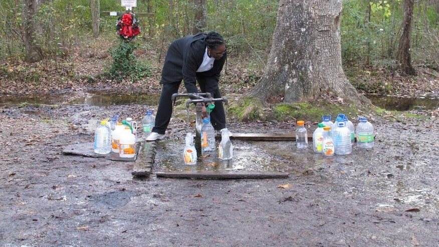 Carolyn Hayes fills up as many bottles as she can from the Healing Springs at God's Acre on Friday, Dec. 5, 2014, in Blackville, S.C. People have thought the natural springs have supernatural healing powers ever since four gravely wounded British soldiers recovered after drinking from them in 1781. (AP Photo/Jeffrey Collins)