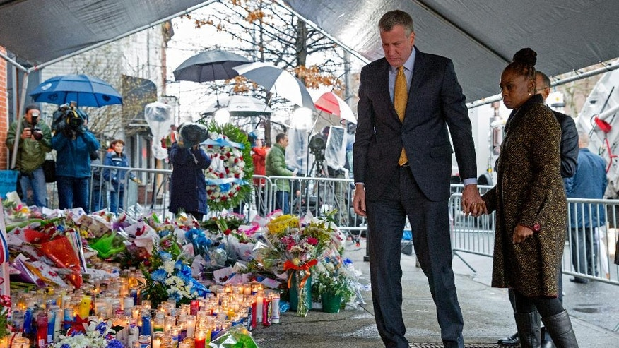 New York City Mayor Bill de Blasio and his wife, Chirlane McCray, visit a makeshift memorial, Tuesday, Dec. 23, 2014, near the site where New York Police Department officers Rafael Ramos and Wenjian Liu were murdered in the Brooklyn borough of New York. Police say Ismaaiyl Brinsley ambushed the two officers in their patrol car in broad daylight Saturday, fatally shooting them before killing himself inside a subway station. (AP Photo/Craig Ruttle)