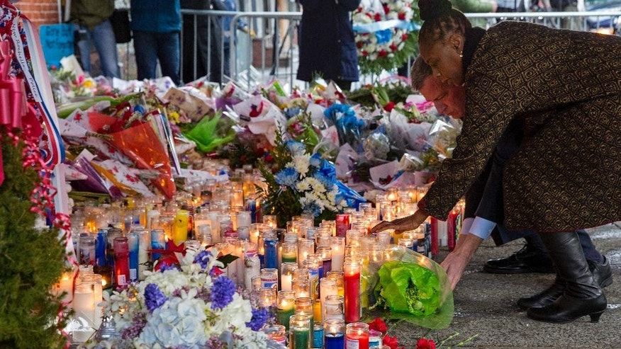 New York City first lady Chirlane McCray and her husband, Mayor Bill de Blasio, lay a bouquet, Tuesday, Dec. 23, 2014, near the site where New York Police Department officers Rafael Ramos and Wenjian Liu were murdered in the Brooklyn borough of New York. Police say Ismaaiyl Brinsley ambushed the two officers in their patrol car in broad daylight Saturday, fatally shooting them before killing himself inside a subway station. (AP Photo/Craig Ruttle)