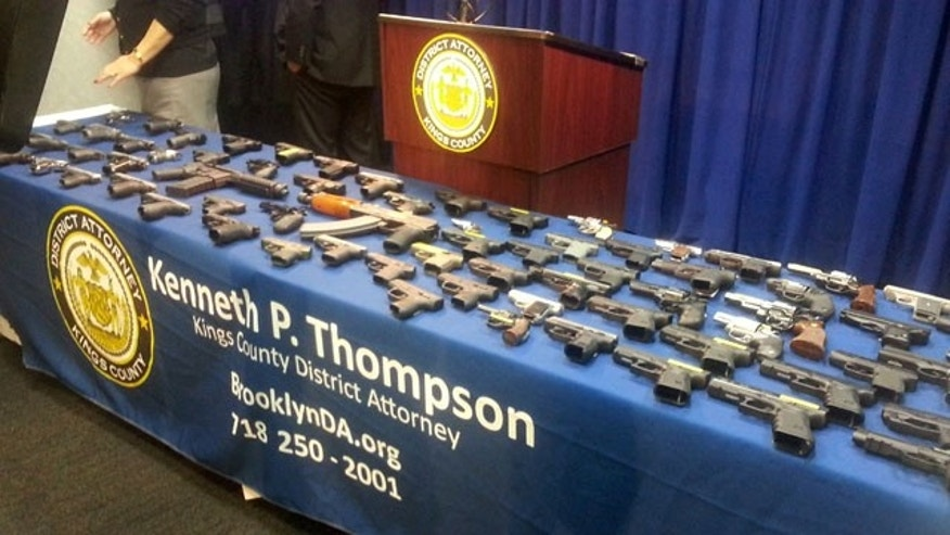 Dec. 23, 2014: In this photo provided by the Brooklyn District Attorney's Office, a collection of handguns and two assault rifles fill a table during a news conference. (AP Photo/Brooklyn District attorney's Office, Christina Carrega-Woodby)