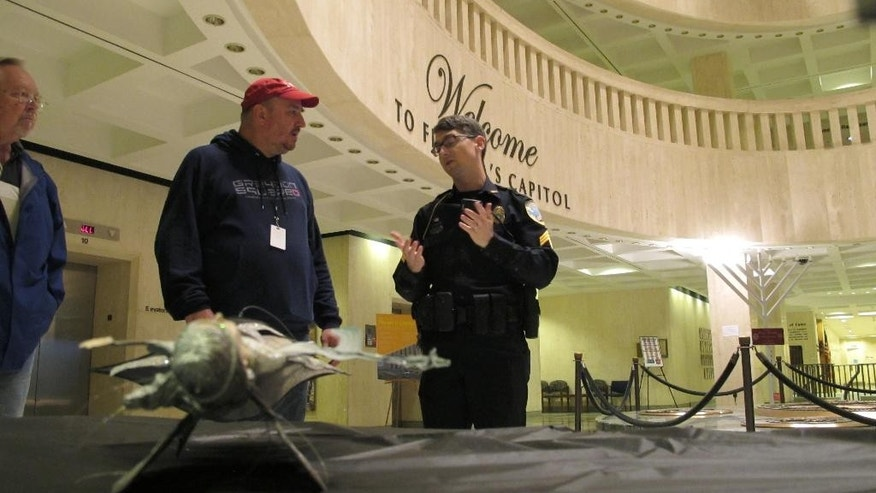 John Porgal, regional director of the American Atheists, second from left, talks with a Capitol Police officer after his Satanic Temple holiday display was damaged in the statehouse rotunda, Tuesday, Dec. 23, 2014, in Tallahassee, Fla. A woman damaged the Satanic display a day after an atheist group put it up as a counter to a nativity scene that was set up by a Christian group. (AP Photo/Brendan Farrington)