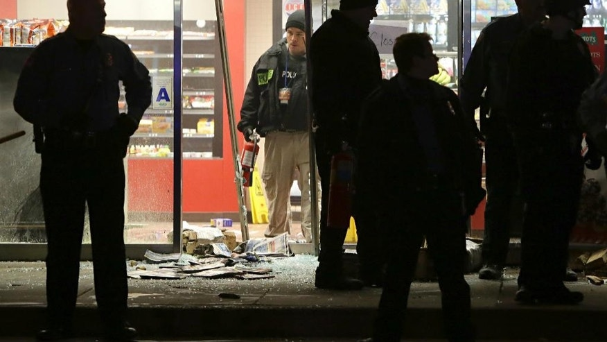 A police officer with a fire extinguisher stands in the broken out entry to a QuikTrip on Wednesday, Dec. 24, 2014, following a shooting nearby Tuesday in Berkeley, Mo. St. Louis County police say a man who pulled a gun and pointed it at an officer has been killed. (AP Photo/St. Louis Post-Dispatch, David Carson)