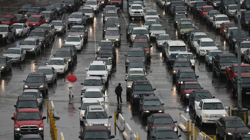 FILE - In this Dec. 3, 2014 file photo, cars wait to enter the United States from Tijuana, Mexico through the San Ysidro port of entry in San Diego. San Diego police say a 40-year-old man died after a border inspector shot him with a stun gun at the nation's busiest crossing. Police said Thursday, Dec. 25, 2014 that the man jumped over a counter and attacked an inspector after being escorted to a separate area for questioning at the San Ysidro port of entry between San Diego and Tijuana, Mexico and a records check revealed he was wanted on a felony charge. (AP Photo/Gregory Bull)