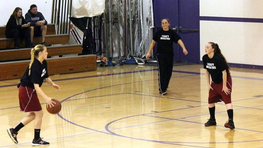 "This photo provided by the Fort Bragg Advocate-News shows Mendocino High School girls basketball wearing the ""I Can't Breathe"" T-shirts before a recent game.  A high school basketball tournament on the Northern California coast has become the latest flashpoint in the ongoing protests over police killings of unarmed black men after a school was disinvited because of concerns its players would wear T-shirts printed with the words ""I Can't Breathe"" during warmups. The athletic director at Fort Bragg High School informed his counterpart at Mendocino High School this week that neither the boys nor girls team would be allowed to participate in the three-day tournament hosted by Fort Bragg High starting Monday, Mendocino Unified School District Superintendent Jason Morse said. (AP Photo/Fort Bragg Advocate-News, Chris Calder)"