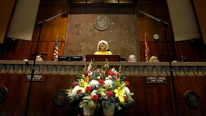 FILE - In this Jan. 13, 2014, file photo, Arizona Gov. Jan Brewer gives her State of the State address in the Arizona House of Representatives at the Arizona Capitol in Phoenix. Brewer fought President Barack Obama on immigration and border security for most of her tenure, earning national prominence by enacting tough laws that were mainly struck down by the courts and famously wagging her finger in the president's face during a meeting on an airport tarmac. But the Republican governor leaves a more nuanced legacy after nearly six years in office, one that saw her inherit a massive deficit at the height of the Great Recession, patch it up and push for economic recovery only to see Arizona sink back into a deficit as she prepares to step down Jan. 5, 2015. (AP Photo/Ross D. Franklin, File)