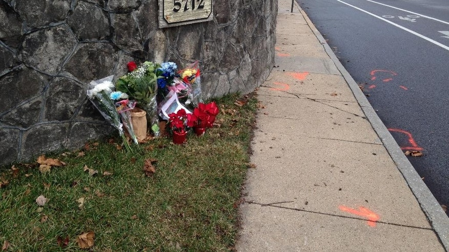 Flowers and messages are shown Monday, Dec. 29, 2014, at the scene of a fatal collision between a car and bicyclist along a Baltimore residential street with a bike lane. The Episcopal Church of Maryland says one of its bishops was driving the car Saturday, Dec. 27, 2014, when it struck cyclist Tom Palermo, fatally injuring him. The Baltimore Police Department is investigating. (AP Photo/Amanda Kell)