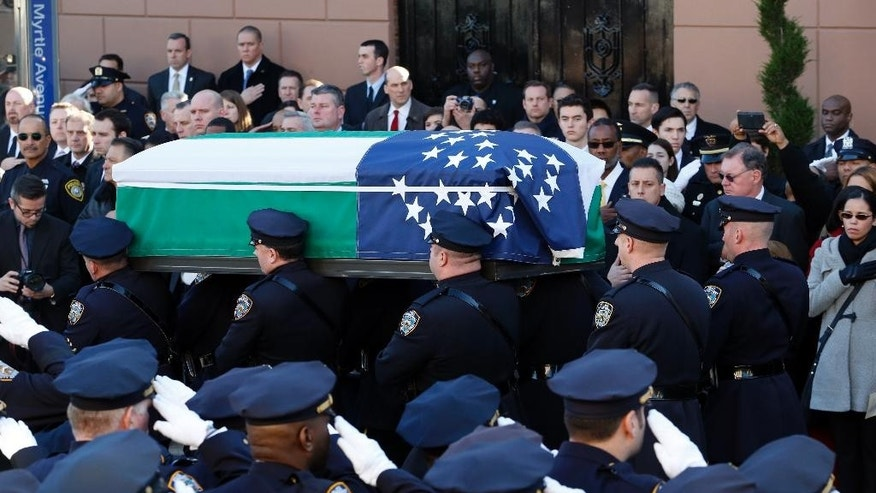 Pallbearers carry the casket of New York City police officer Rafael Ramos following funeral services at Christ Tabernacle Church, in the Glendale section of Queens, Saturday, Dec. 27, 2014, in New York. Ramos and his partner, officer Wenjian Liu, were killed Dec. 20 as they sat in their patrol car on a Brooklyn street. The shooter, Ismaaiyl Brinsley, later killed himself. (AP Photo/Julio Cortez)