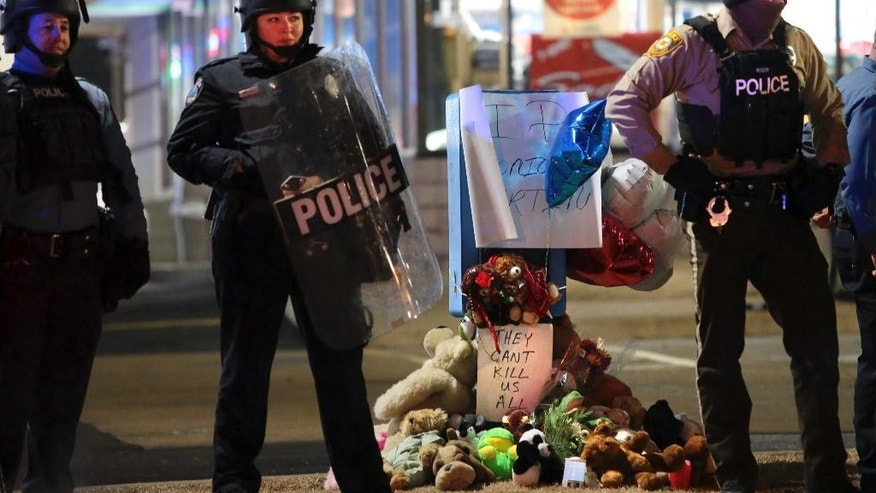 FILE - In a Wednesday, Dec. 24, 2014 file photo, police guard the entrance to a gas station in front of a memorial to Antonio Martin, in Berkeley, Mo. Officials said Tuesday, Dec. 30, 2014 that an internal police investigation confirmed that Martin pointed a gun at an officer who shot him to death in a convenience store parking lot in suburban St. Louis on Dec. 23.  (AP Photo/St. Louis Post-Dispatch, Robert Cohen, File)