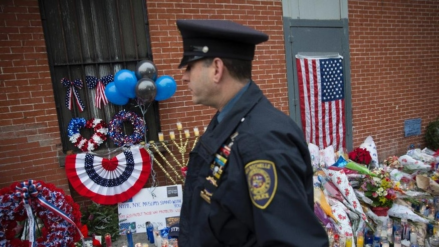 FILE- In this Dec. 22, 2014, file photo, a member of the New Rochelle, N.Y., police department visits a makeshift memorial, near the site where New York Police Department officers Rafael Ramos and Wenjian Liu were murdered in the Brooklyn borough of New York. Their attacker, Ismaaiyl Brinsley, had referenced in online posts the high-profile killings by white police officers of unarmed black men, specifically Michael Brown in Ferguson, Missouri, and Eric Garner in the New York borough of Staten Island. (AP Photo/John Minchillo, File)