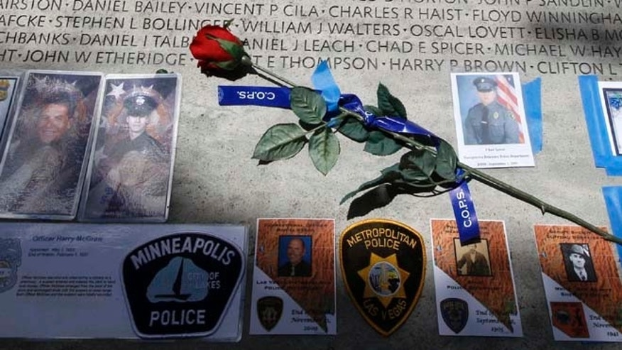 May 13, 2013: A rose is placed at the wall with the names of fallen police officers at the National Law Enforcement Officers Memorial in Washington during the National Police Week. The number of law enforcement officers killed by firearms in the U.S. jumped by 56 percent this year and included 15 ambush assaults, according to a report released Tuesday.