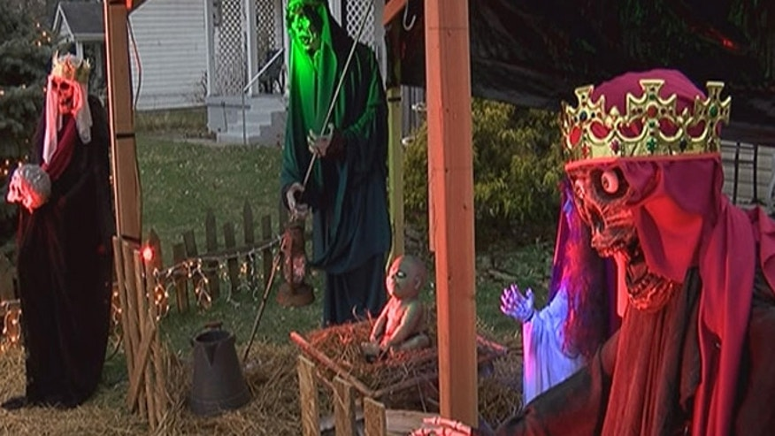The nativity scene features life-size figures and a zombie baby Jesus, with pale skin and pure white eyes. At night, the figures are illuminated by red and green lights.